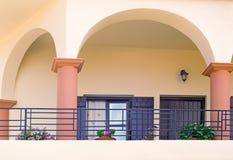Detalhe da fachada de uma casa velha com balcões e um sol aw Foto de Stock
