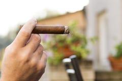 Detalhe da mão de um homem de fumo que guarda um charuto ardente com Fotografia de Stock Royalty Free