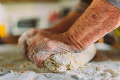 Detalhe das mãos da mulher adulta enrugada que preparam a massa Imagem de Stock