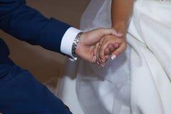 Detalhe das mãos dos pares durante a cerimônia da igreja imagens de stock