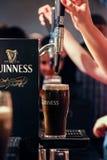 Detalhe das mãos dos peopleque derramam uma pinta de guinness no contador de guinness na cervejaria do depósito de Guinness Fotografia de Stock Royalty Free