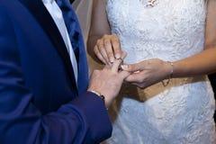 Detalhe das mãos neste momento em qual a noiva põe o anel dos groom's fotografia de stock
