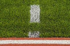 Detalhe das pistas de borracha da pista de atletismo com grama artificial Imagens de Stock Royalty Free