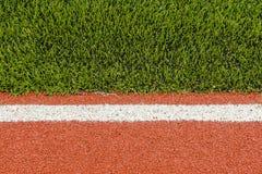 Detalhe das pistas de borracha da pista de atletismo com a grama artificial Imagem de Stock