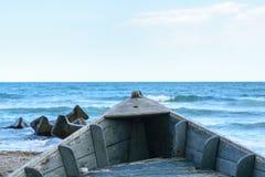 Detalhe de barco de madeira velho na areia da praia com o mar obscuro da água azul no fundo imagens de stock