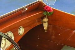Detalhe de barco de madeira da velocidade do vintage com o vaso de cristal no suporte do vaso com uma rosa vermelha Fotos de Stock Royalty Free