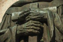 Detalhe de bronze da estátua de mãos do padre que guardam uma cruz em Caceres imagens de stock