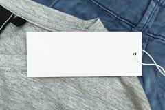 Detalhe de calças de ganga e de t-shirt cinzento com as etiquetas vazias brancas, fim acima foto de stock