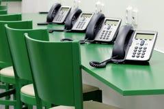 Detalhe de centro de atendimento verde com telefones do IP Imagens de Stock