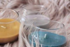 Detalhe de decoração da casa com três velas de cores cinzentas e azuis amarelas imagens de stock royalty free