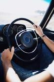 Detalhe de duas mãos que guardam um volante de madeira do vintage no preto Fotografia de Stock Royalty Free
