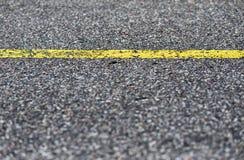 Detalhe de estrada asfaltada com linha amarela Imagens de Stock Royalty Free