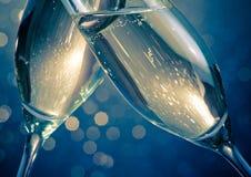 Detalhe de flautas de champanhe com bolhas douradas no fundo claro azul do bokeh Fotografia de Stock