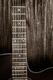 Detalhe de guitarra acústica no estilo do vintage no fundo de madeira Foto de Stock