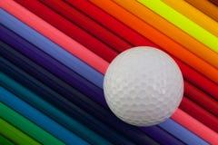 Detalhe de lápis e de bola de golfe coloridos do arco-íris na mesa Imagem de Stock Royalty Free