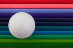 Detalhe de lápis e de bola de golfe coloridos do arco-íris na mesa Imagens de Stock Royalty Free