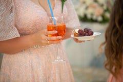 Detalhe de mão da mulher com a bebida do vermelho do vidro de cocktail fotos de stock royalty free
