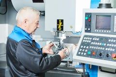 Detalhe de medição do trabalhador industrial perto da máquina de trituração do cnc Imagem de Stock Royalty Free