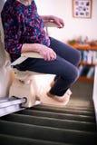 Detalhe de mulher superior que senta-se no elevador da escada em casa para ajudar a mobilidade fotografia de stock