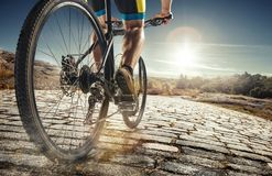 Detalhe de pés do homem do ciclista que montam o Mountain bike na fuga exterior na estrada secundária imagens de stock royalty free