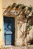 Detalhe de parede do ocre da casa com porta azul dentro e árvore da sombra Imagem de Stock
