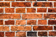 Detalhe de parede de tijolo vermelho suja velha e resistida marcada pela exposição longa aos elementos como o fundo da textura imagem de stock royalty free