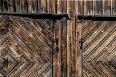 Detalhe de portas de celeiro de madeira velhas rústicas de pranchas ásperas e resistidas com a dobradiça e o fechamento oxidados  fotografia de stock royalty free