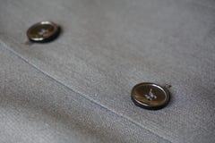 Detalhe de um botão costurado ao terno cinzento fino Fotografia de Stock