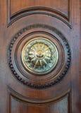 Detalhe de um botão dourado e de um portal de madeira antigo imagem de stock royalty free