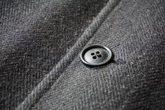 Detalhe de um botão escuro que prende o revestimento do inverno do osso de peixes Fotos de Stock Royalty Free