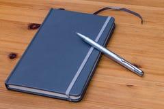 Detalhe de um caderno e de uma pena na tabela de madeira Imagens de Stock