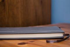 Detalhe de um caderno na tabela de madeira Imagem de Stock