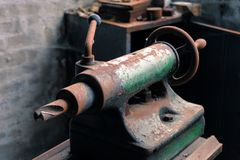 Detalhe de um torno oxidado e oleoso antigo em um salão industrial abandonado imagens de stock royalty free