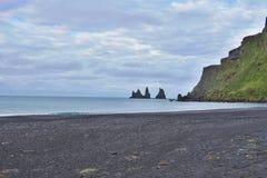 Detalhe de uma areia preta na praia escura famosa na cidade islandêsa Vik com os penhascos da rocha no oceano Imagens de Stock