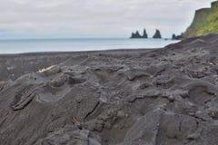 Detalhe de uma areia preta na praia escura famosa na cidade islandêsa Vik com os penhascos da rocha no oceano Fotos de Stock