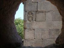 Detalhe de uma parede com uma cruz armênia graven vista por uma janela de pedra profunda redonda, Armênia fotografia de stock