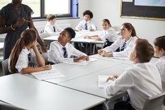 Detalhe de uniforme fêmea de Helping Students Wearing do tutor da High School assentado em torno das tabelas na lição imagens de stock