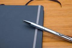 Detalhe do caderno com a pena no fundo de madeira Imagem de Stock Royalty Free