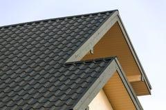 Detalhe do close-up de parte superior moderna nova da casa com o telhado verde shingled no fundo claro do céu azul Construção pro imagens de stock