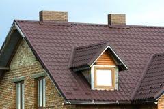 Detalhe do close-up de parte superior nova da casa do tijolo com o telhado marrom da telha, as duas chaminés do tijolo e as janel fotografia de stock royalty free