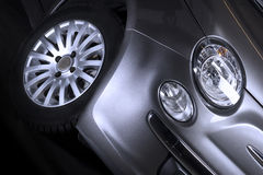 Detalhe do farol e do pneumático dianteiros de um carro Fotografia de Stock