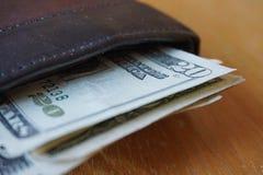 Detalhe dos dólares americanos, cédulas introduzidas na carteira de couro Foto de Stock