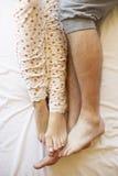 Detalhe dos pés do par que relaxam na cama foto de stock royalty free