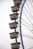 Detalhe e cabines da roda de Ferris em um céu nebuloso e em um branco Fotografia de Stock