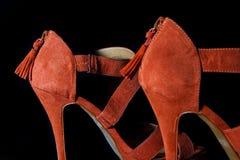 Detalhe em sapatas fêmeas vermelhas dos saltos altos em um fundo preto Imagens de Stock Royalty Free