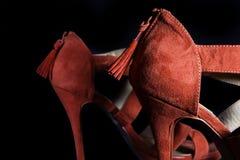 Detalhe em sapatas fêmeas vermelhas dos saltos altos em um fundo preto Fotografia de Stock Royalty Free