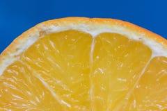 Detalhe em uma laranja da fatia em um fundo azul Fotos de Stock Royalty Free