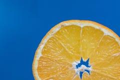 Detalhe em uma laranja da fatia em um fundo azul Foto de Stock Royalty Free