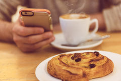 Detalhe a imagem do café bebendo e de guardar do homem unrecognisable o telefone esperto ao comer o café da manhã no restaurante Fotografia de Stock