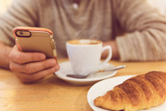 Detalhe a imagem do café bebendo e de guardar do homem unrecognisable o telefone esperto ao comer o café da manhã no restaurante Foto de Stock Royalty Free
